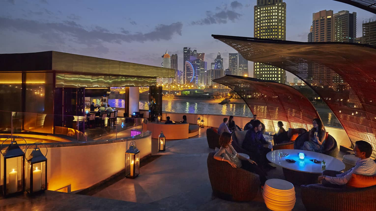Nobu Doha patio at night with glowing lanterns around bar, table, city skyline in background