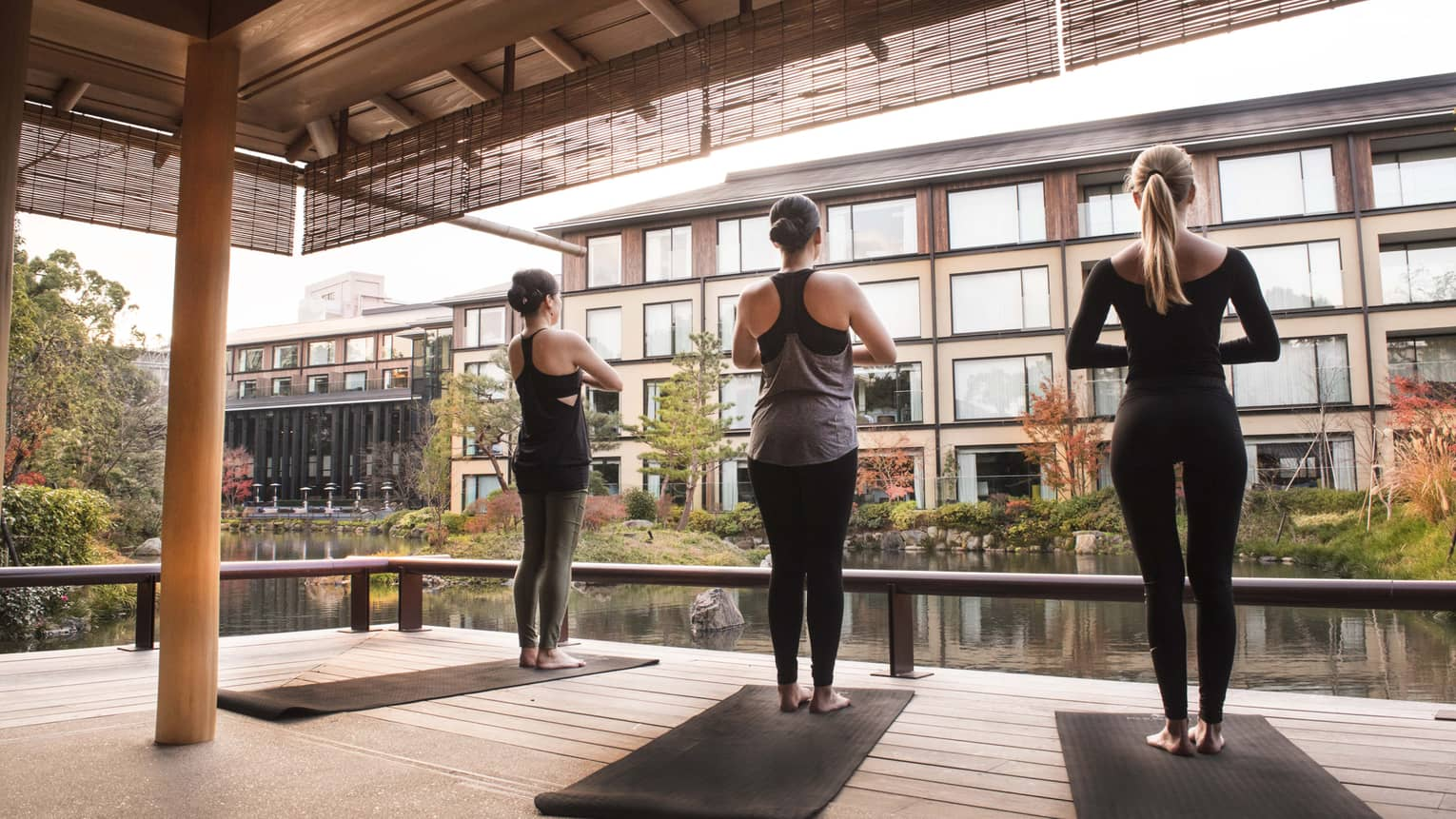 Back of three women wearing fitness clothes standing in yoga pose, facing buildings