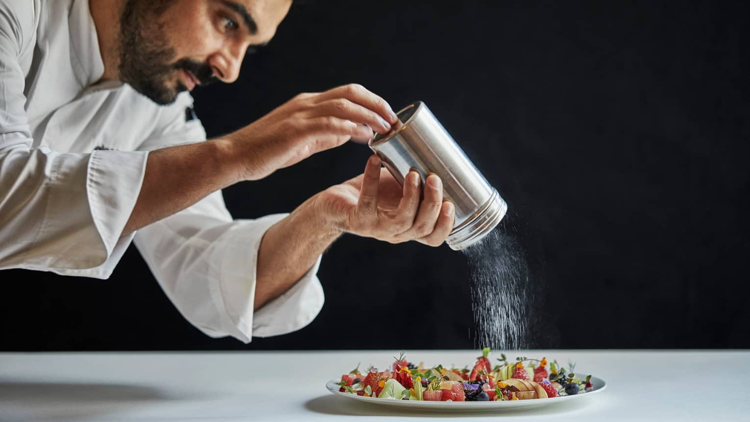 Executive Chef Antonio Mermolia shakes powdered sugar over plate of dessert