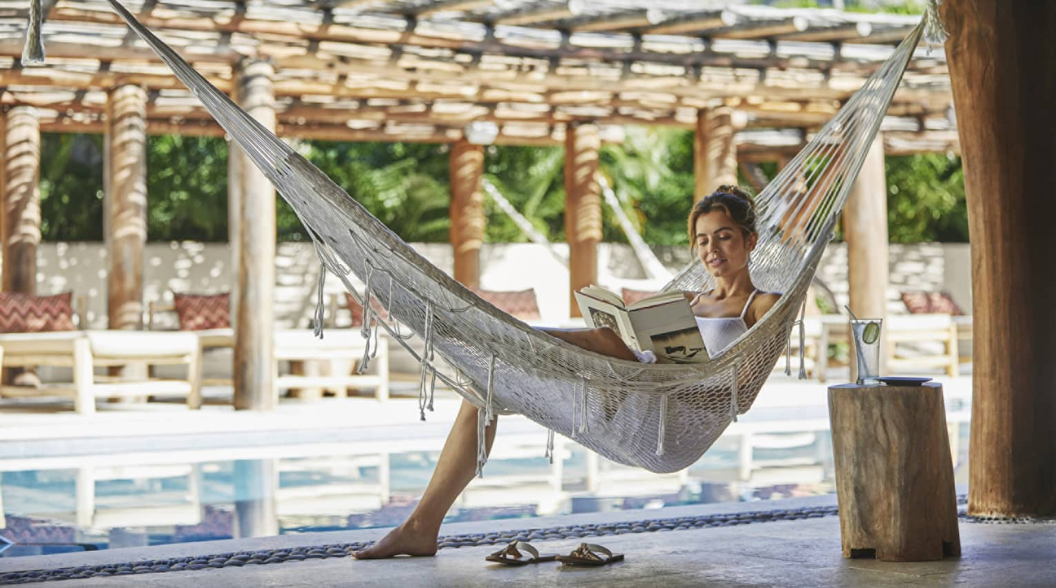 A woman reads a book in a netted hammock by the pool