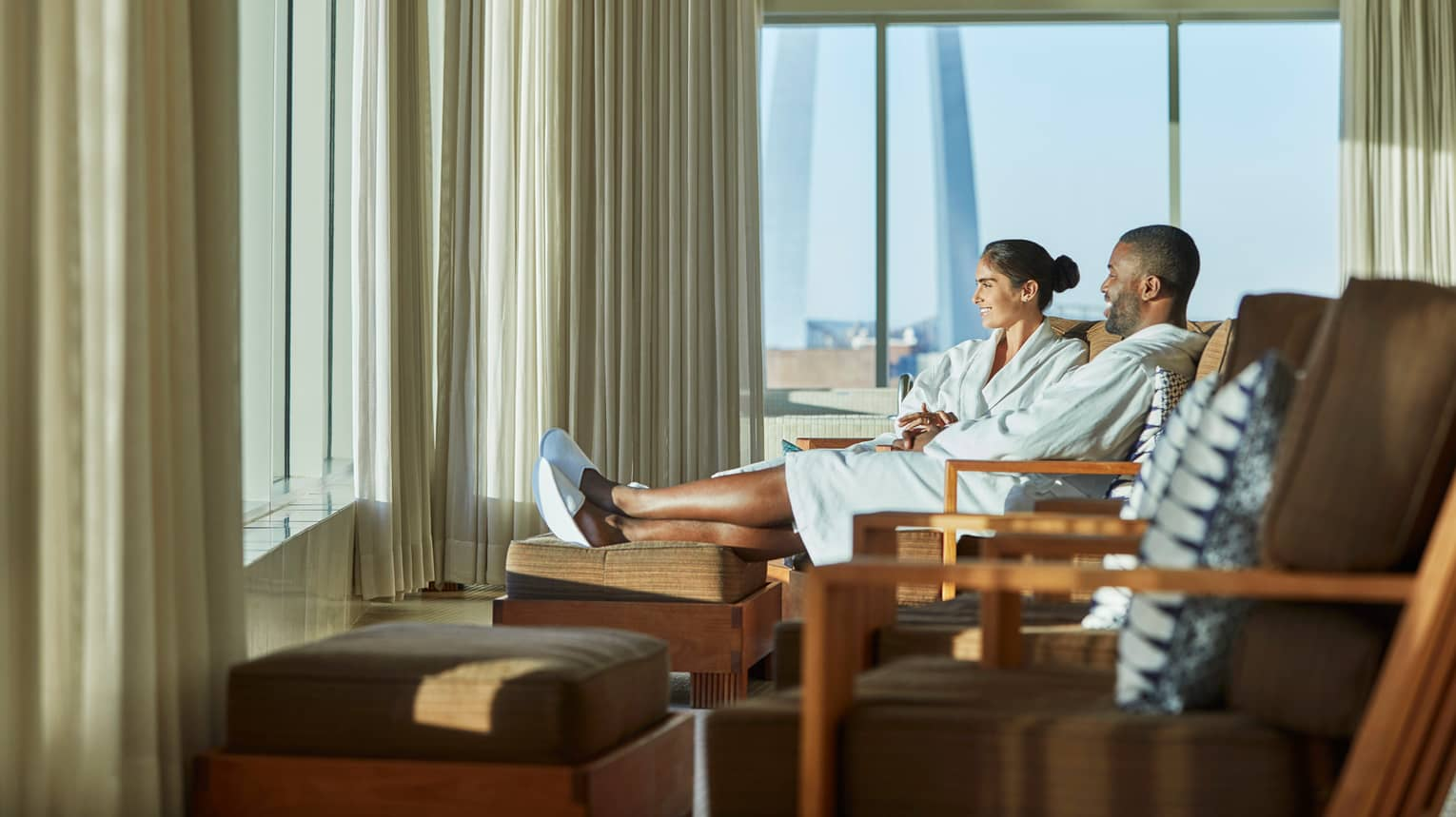 Smiling man and woman in bathrobes and slippers sit on lounge chairs near sunny window
