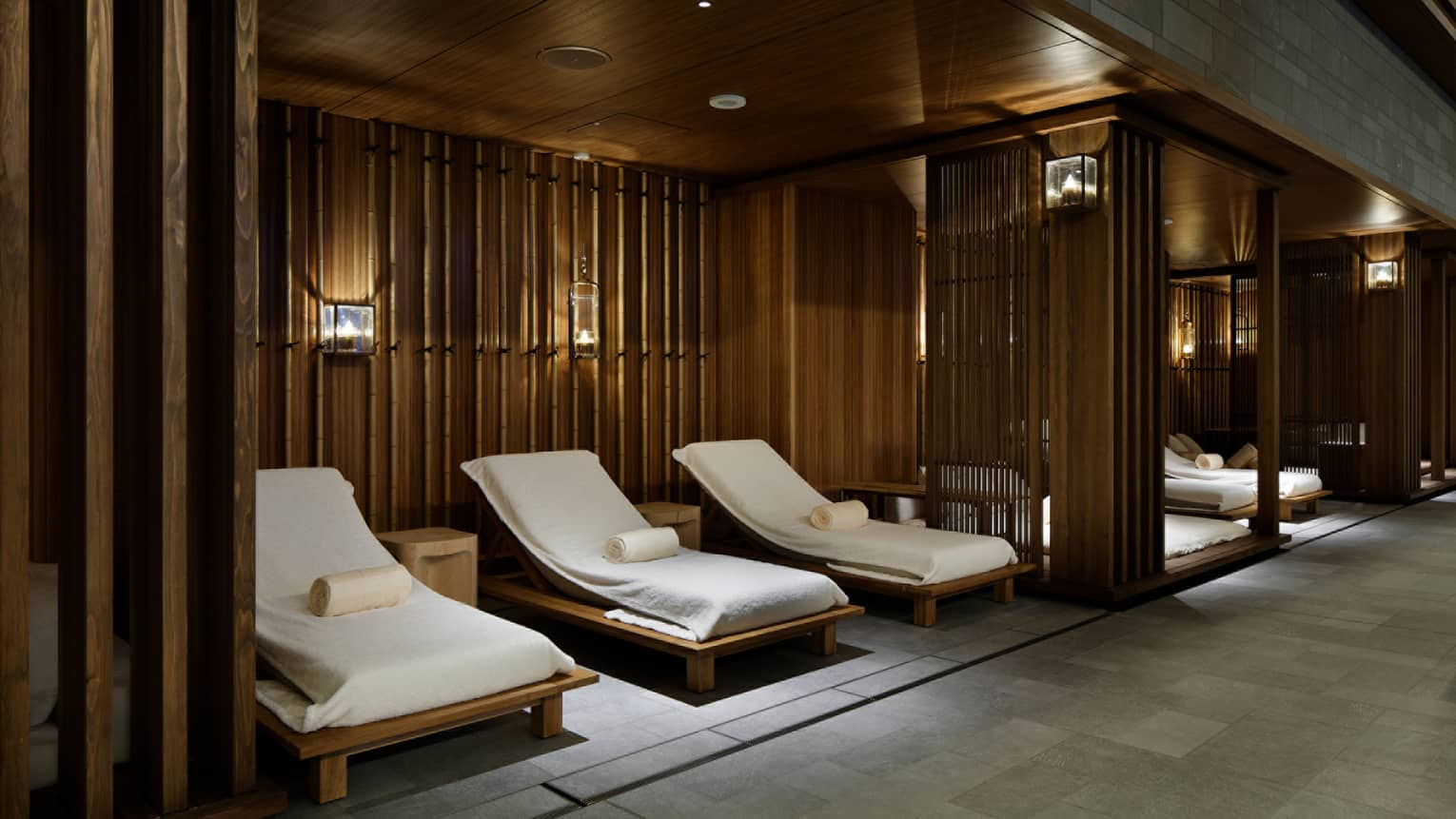 Lounge chairs with white towels under wood walls in spa