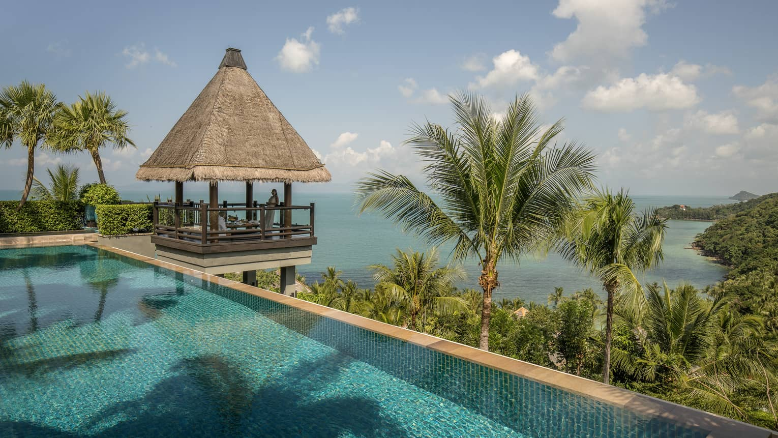 Thatched-roof pavilion at edge of outdoor swimming pool overlooking tropical trees, mountain, ocean