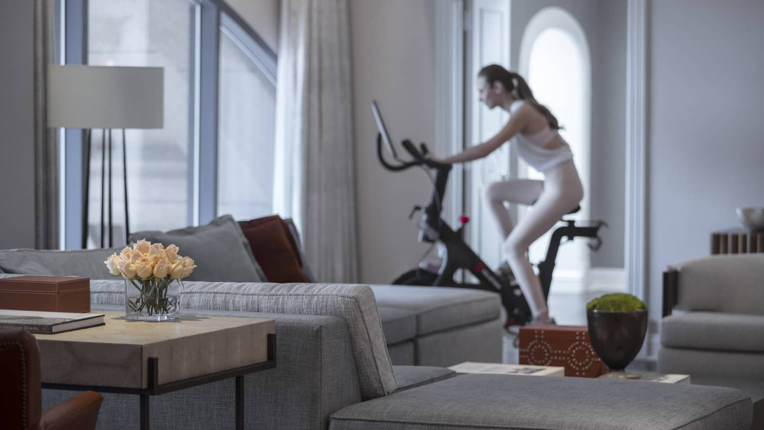 Presidential Suite with beige sectional and woman in white workout gear, riding stationary bike