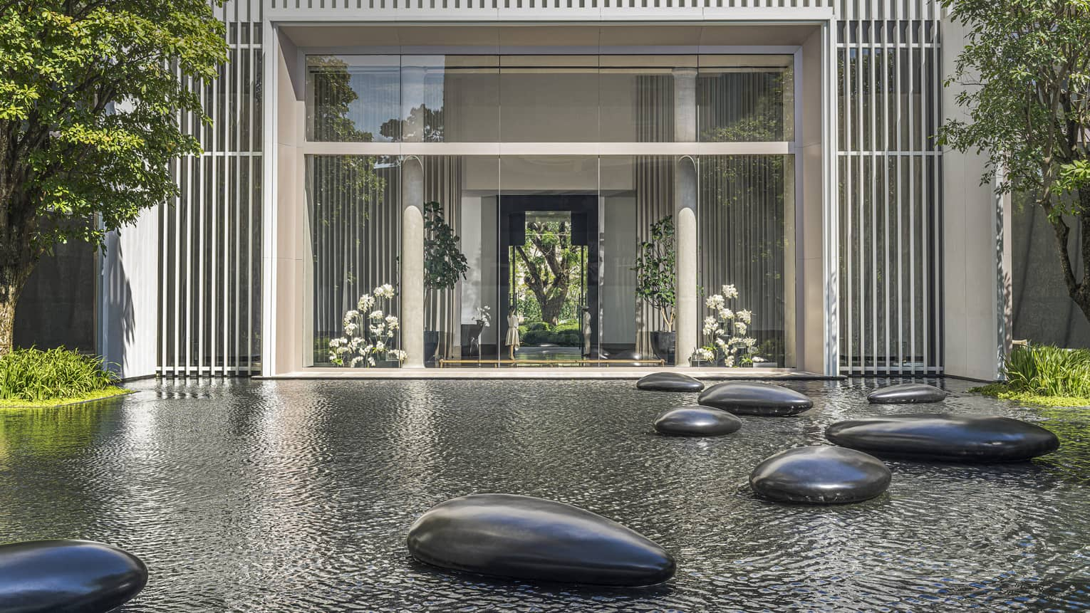 Calm pond in front of hotel with large polished stones scattered throughout
