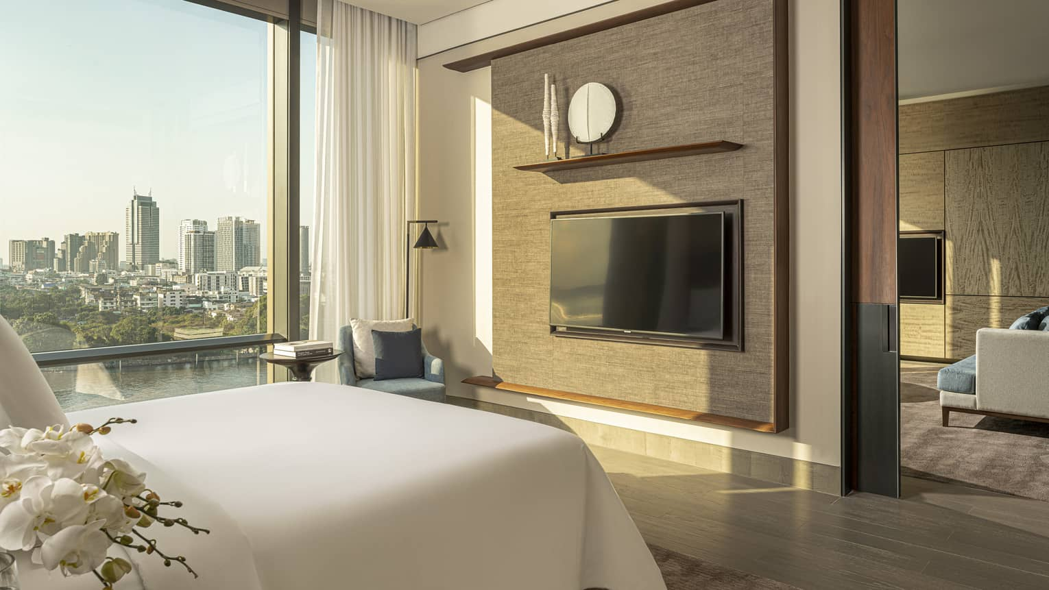 White king bed facing dark tan wall with TV, display shelf beside tall window with river and city view