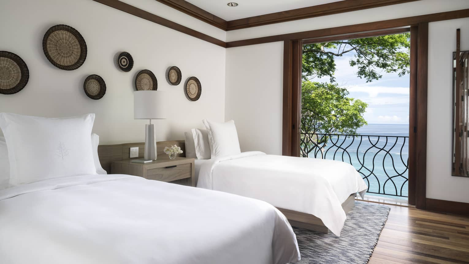 Twin beds with white linens beside open door to iron terrace, ocean views