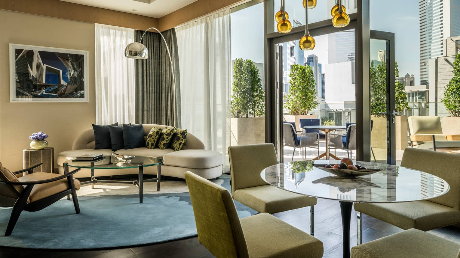 Modern hotel suite living room sofa, glass tables and chairs, open glass door to patio