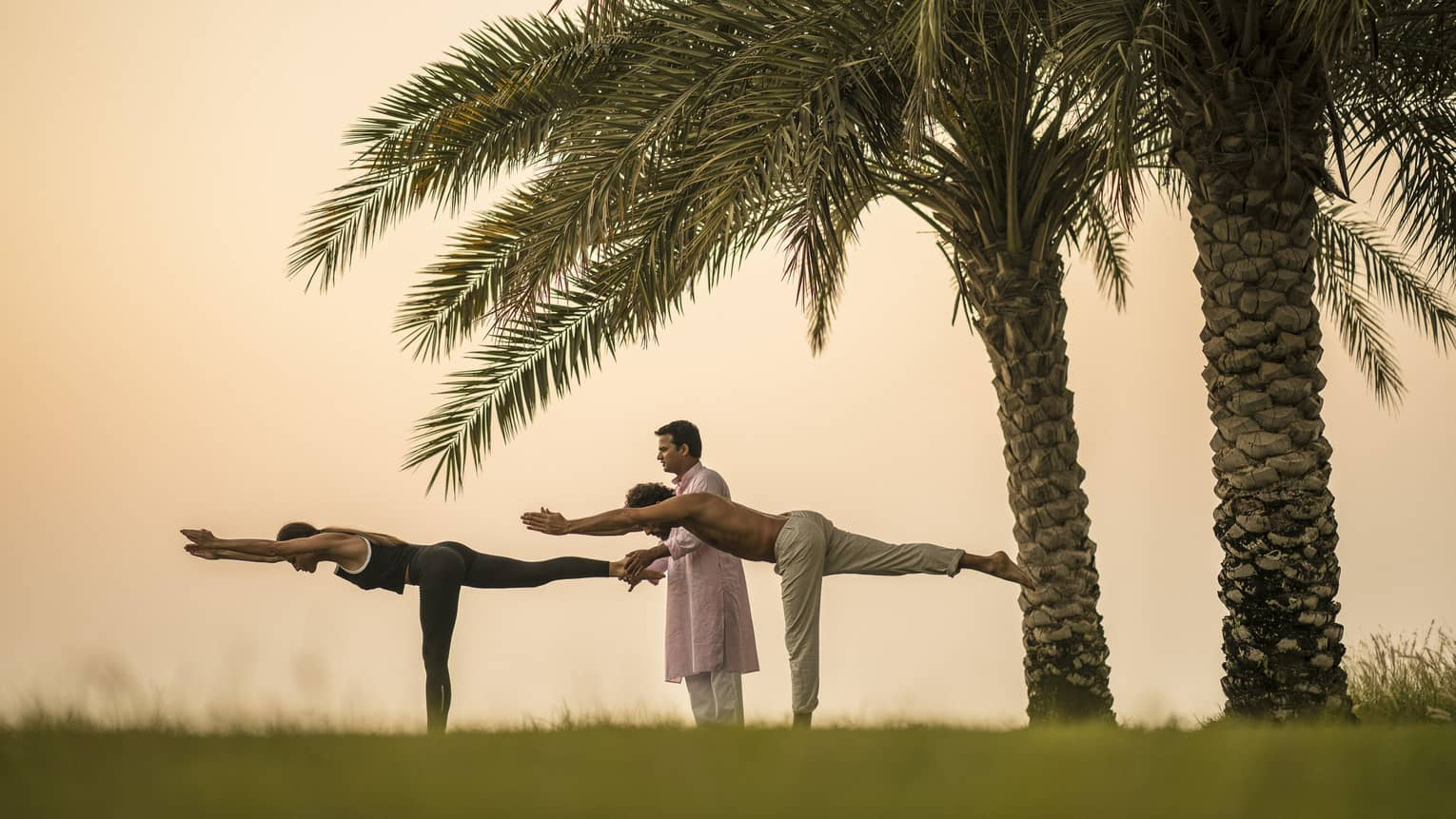 Yogi stands between man and woman doing yoga poses on lawn in front of two palm trees