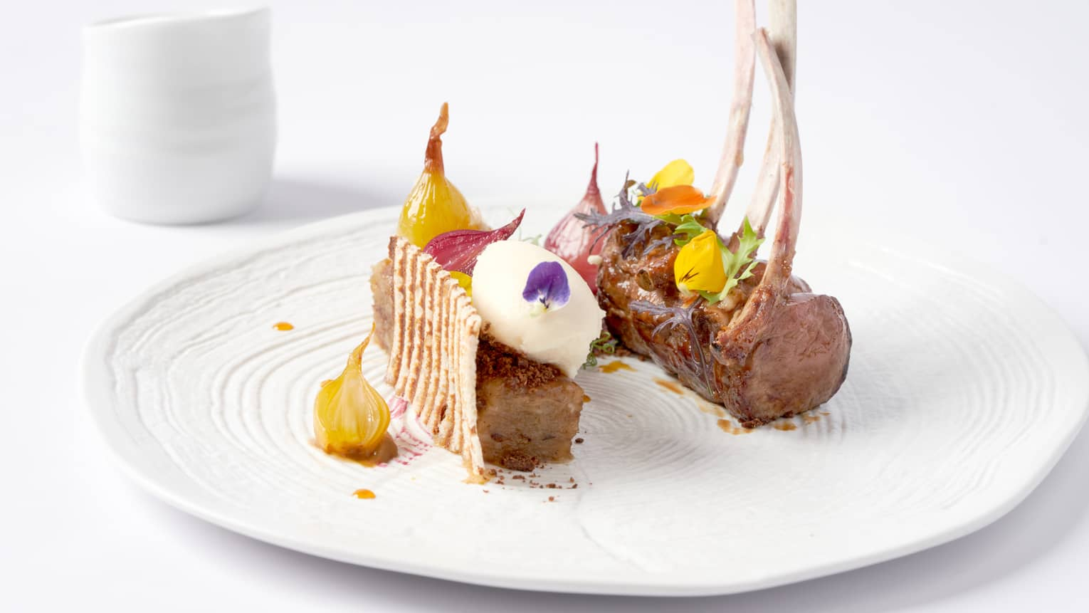 Gourmet rack of lamb topped with candied yellow beets, flowers
