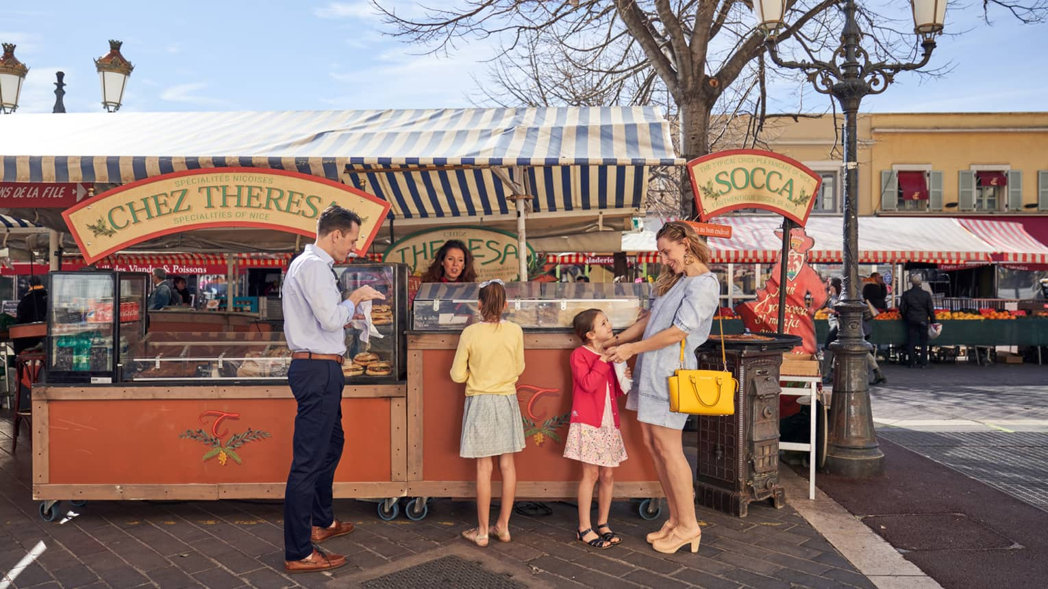Man in blue shirt, black pants with two girls and woman in dresses at market farm stand)