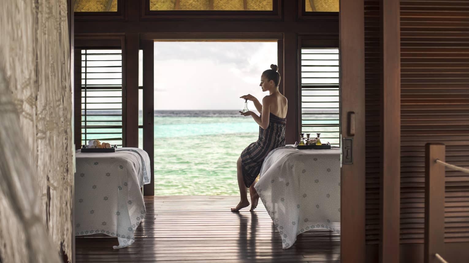 A woman leans against a spa table overlooking the ocean at The Island Spa Treatment Room.
