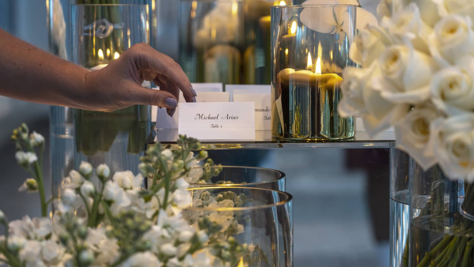 Hand placing banquet name card on table near vases with candles, white flowers