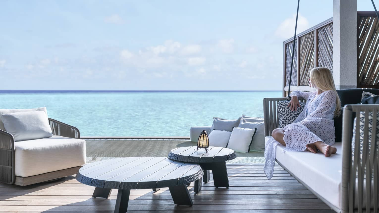 A guest relaxes on a swinging bench on a patio overlooking the ocean