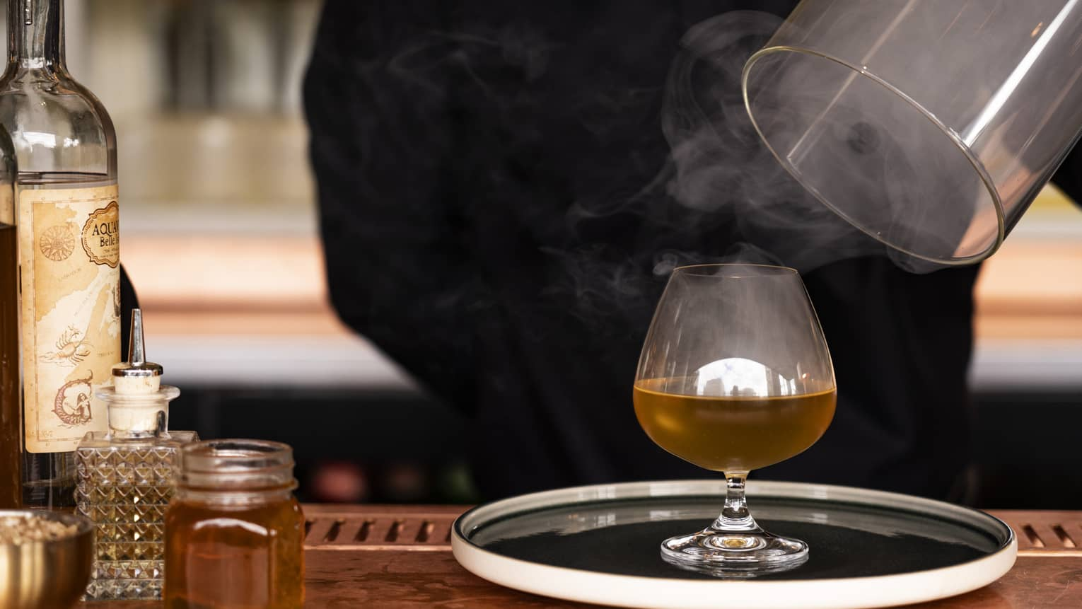 Bartender lifts cover from platter with steaming Old Gods Cocktail