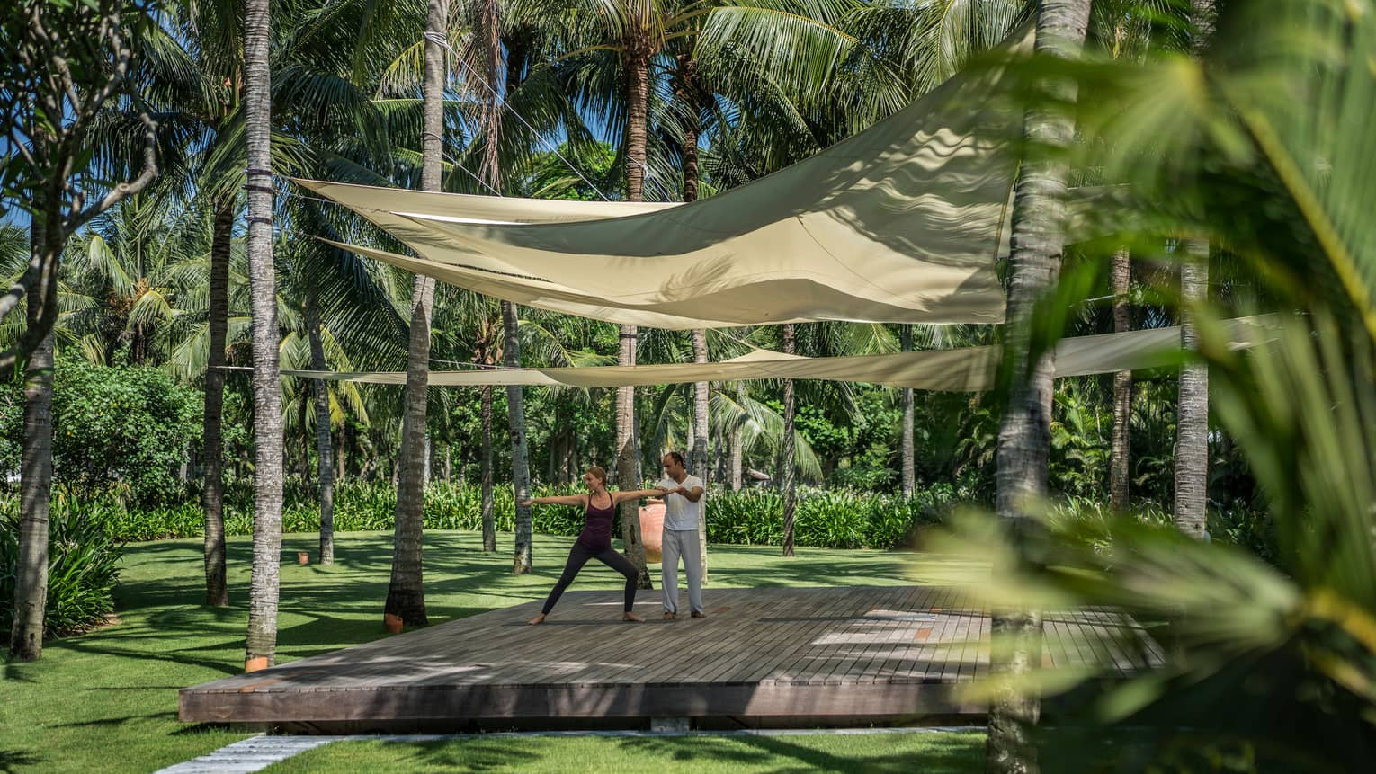Yogi helps two people with yoga poses on wood platform under canopies