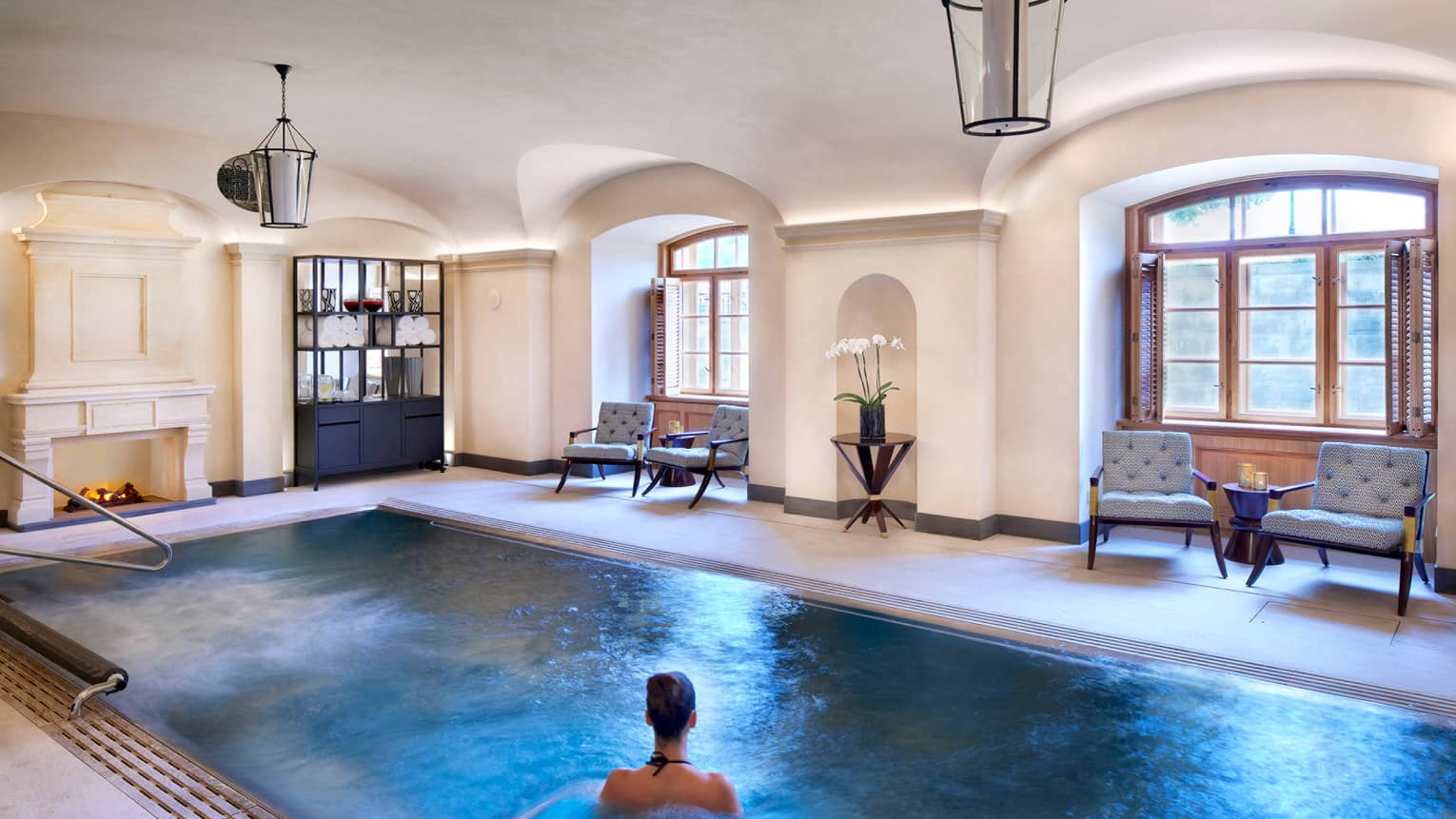 Woman wades in blue water of indoor Vitality Pool at AVA Spa under lanterns, sunny windows