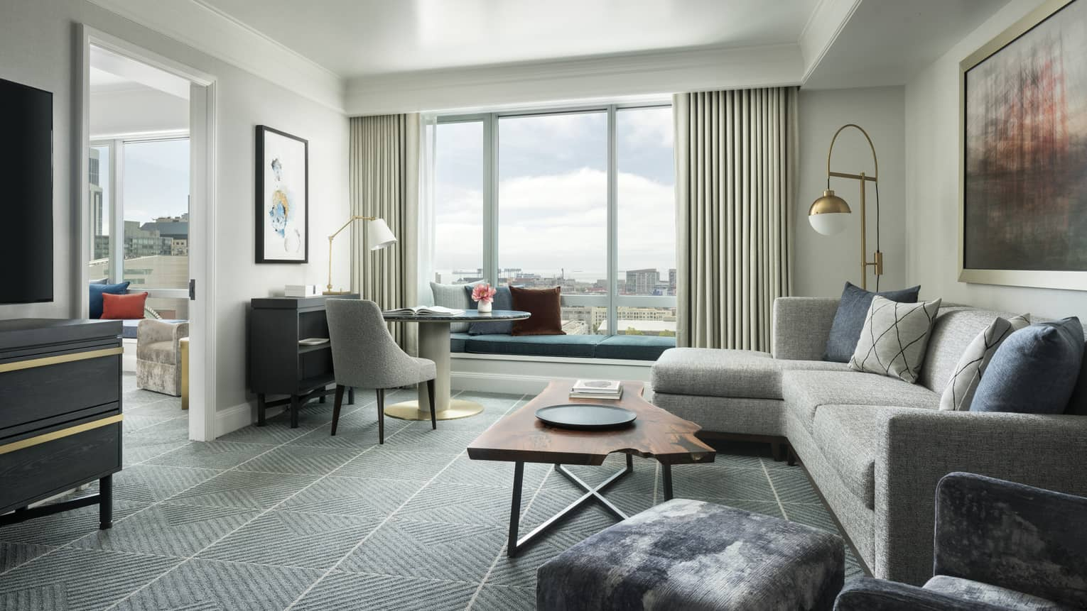 Hotel suite separate living room with retro-style L-shaped grey sofa and desk chair, live-edge wood coffee table