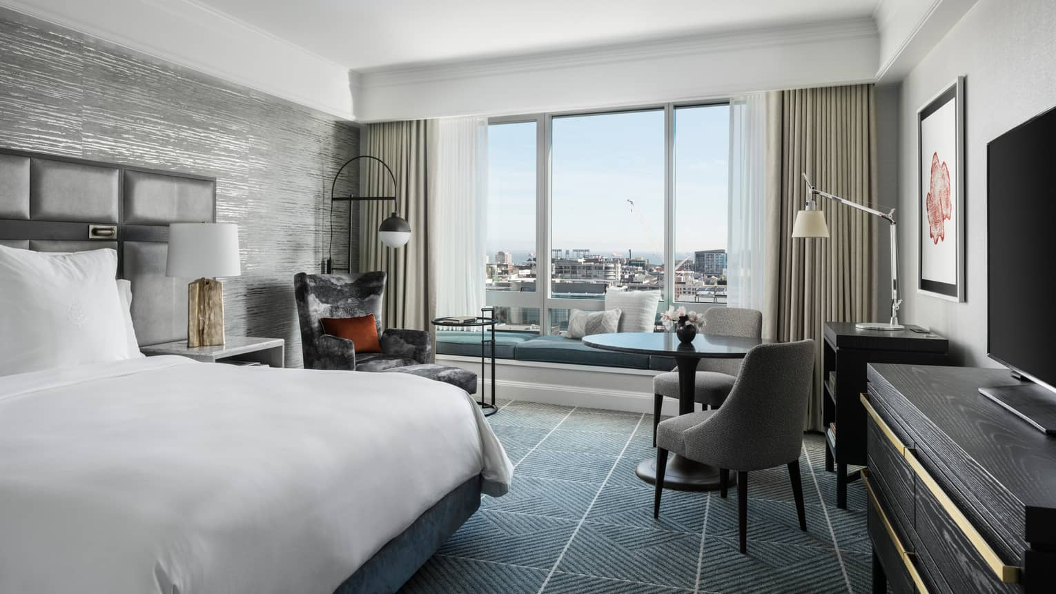 Modern hotel room with king bed, table and two upholstered grey chairs, windows overlooking San Francisco