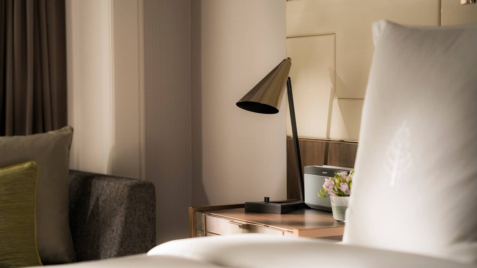 Modern silver lamp on nightstand beside alarm clock, bed