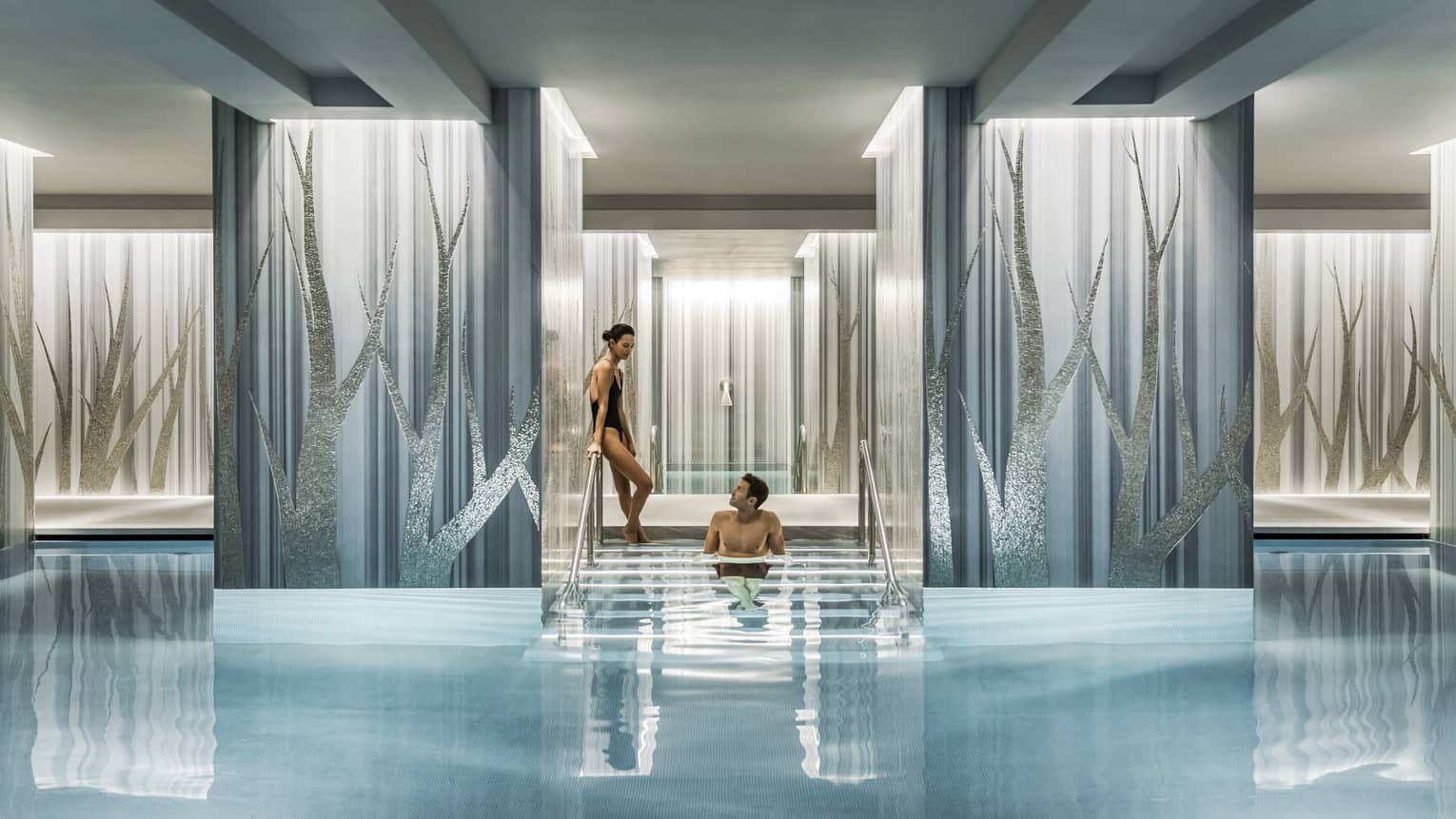Woman in black swimsuit enters serenity pool while man sits on steps between blue and silver columns