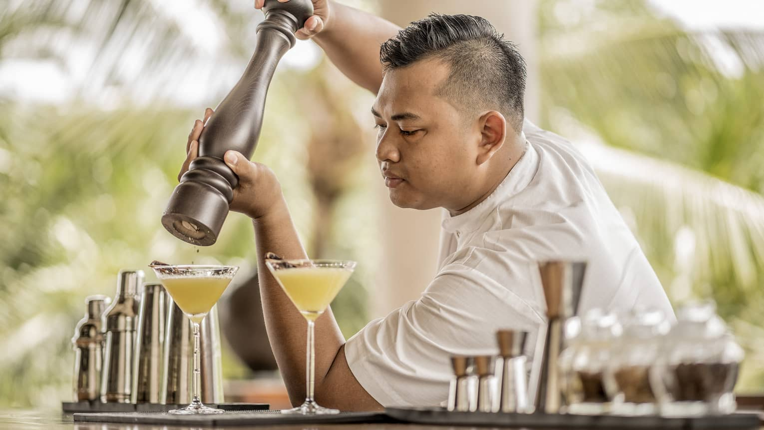 A bartender garnishing a drink with spices in Bali