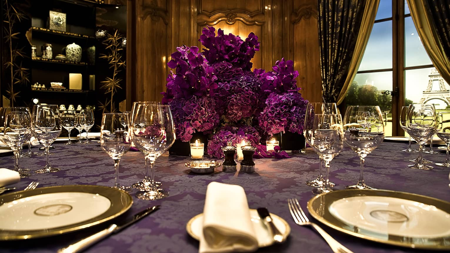Close-up of purple flowers, table linens, gold rimmed dishes in Salon Regence