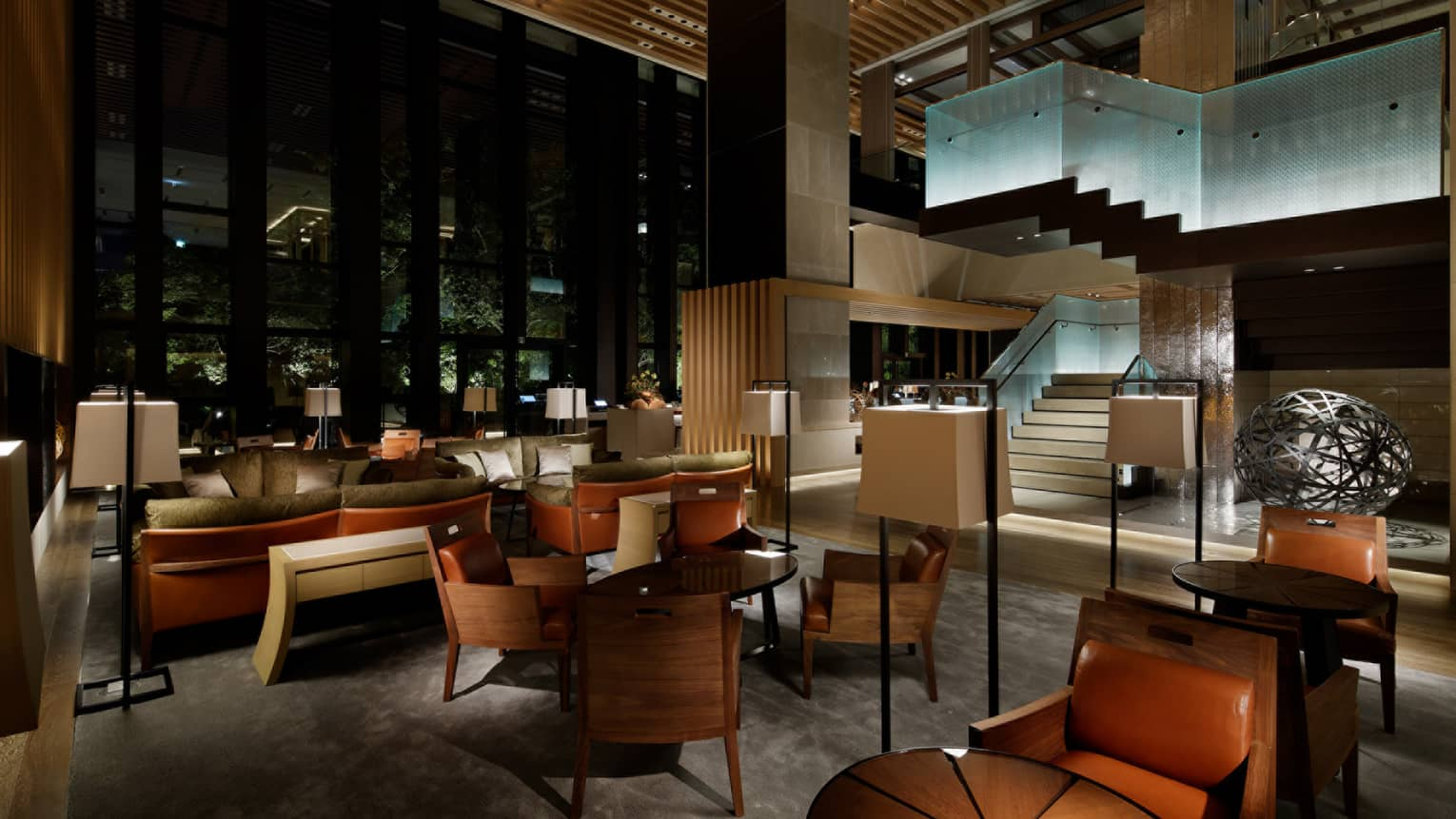 Brasserie dimly-lit dining room, brown leather chairs, tables, sofas under glass staircase