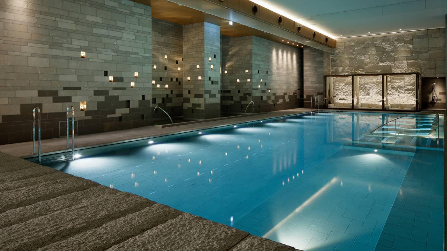 Indoor swimming pool with granite deck, candles along tile wall