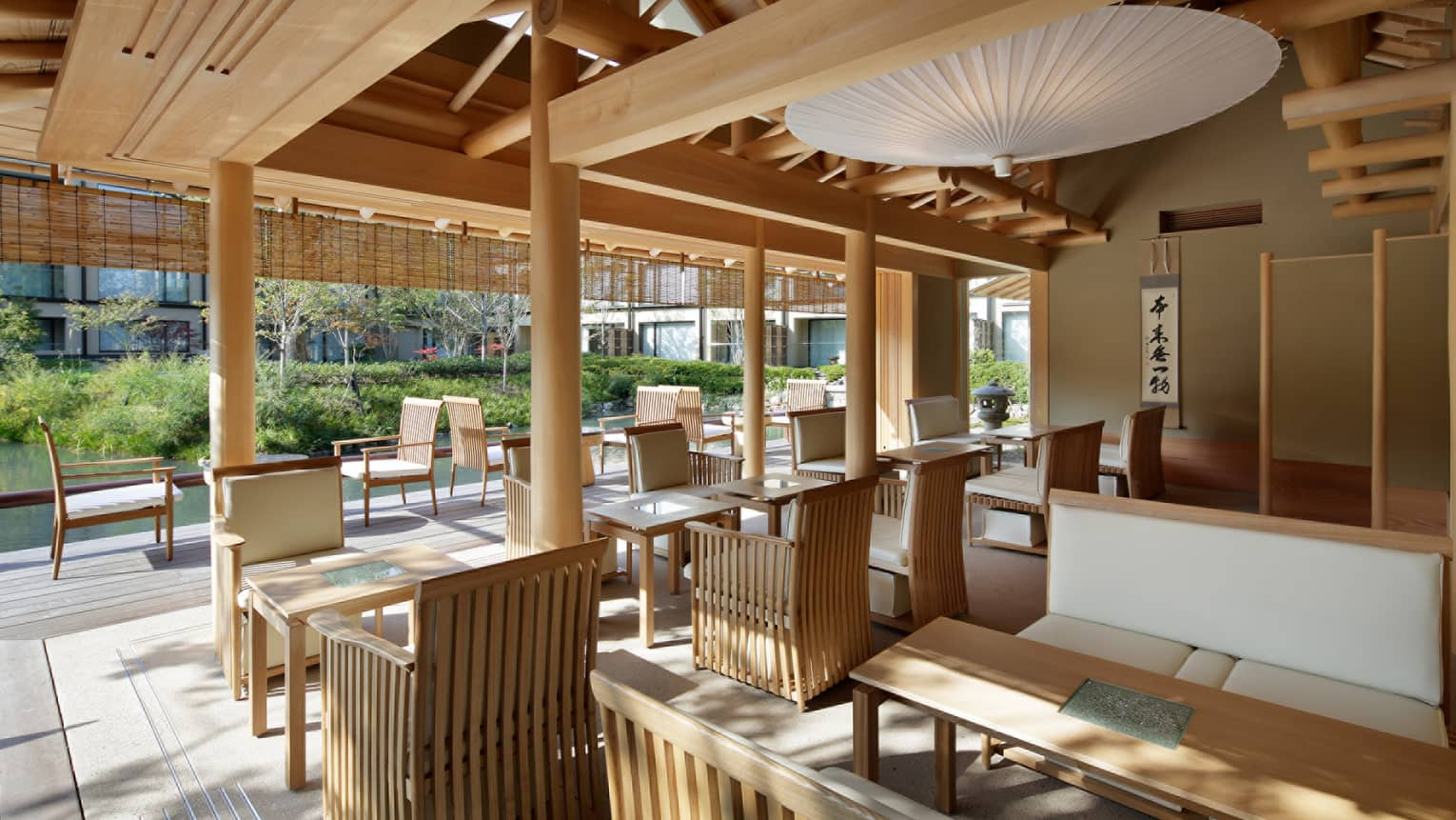 Shakusui-tei sunny patio with wood chairs, tables under white paper umbrella