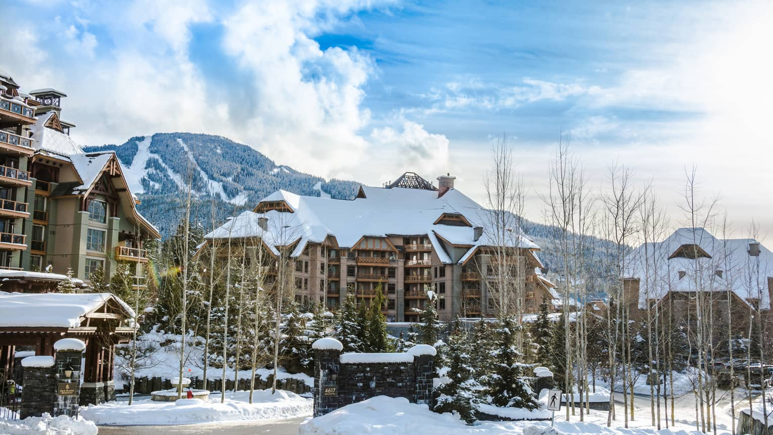 Exterior view of Four Seasons Whistler hotel with snow-covered roof in front of ski hill mountains