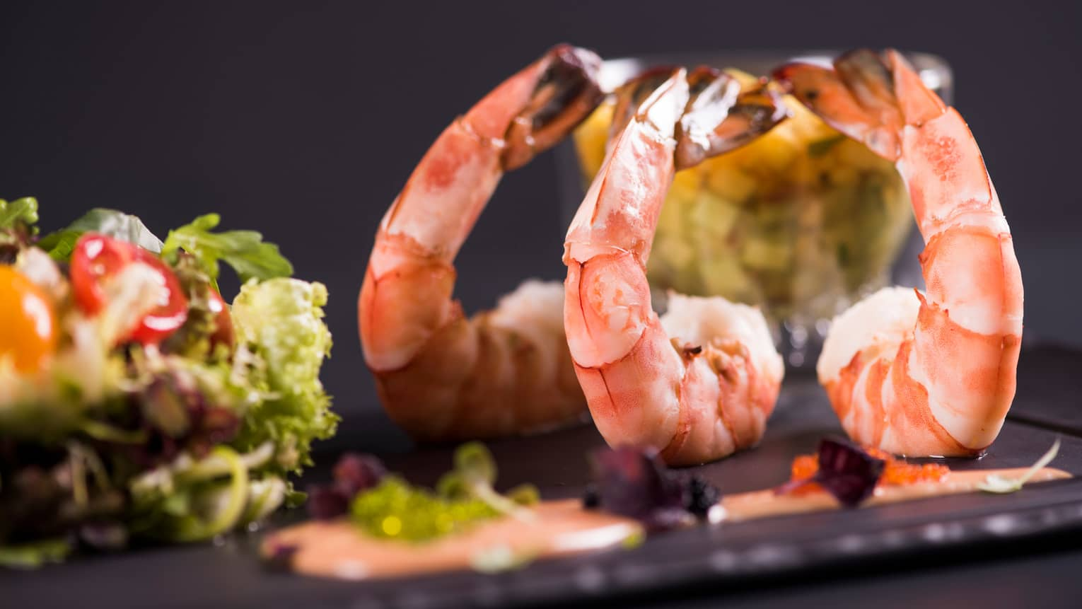 Three large cooked shrimps on black platter in front of salad