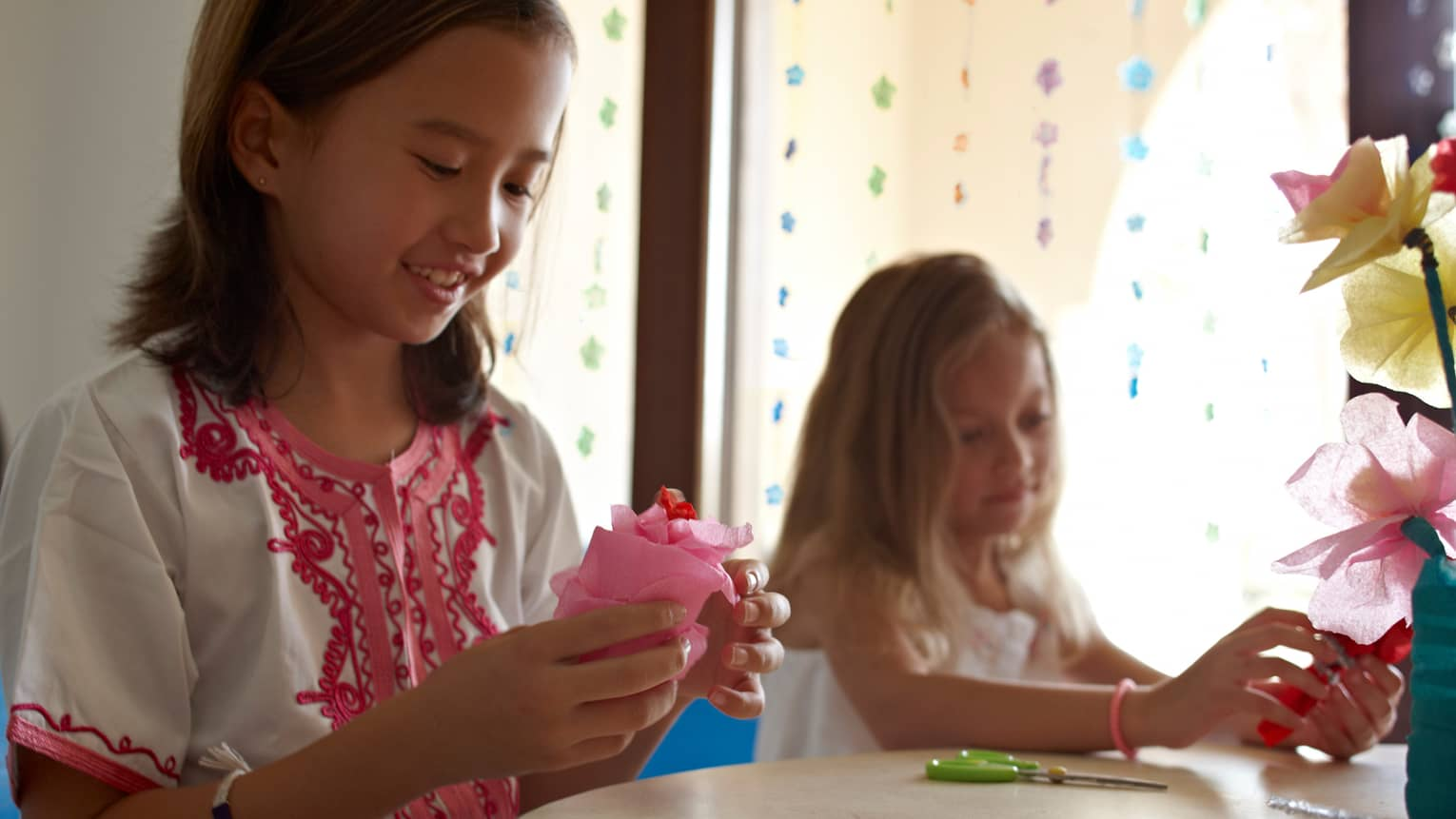 Two young girls at craft table with pink tissue paper