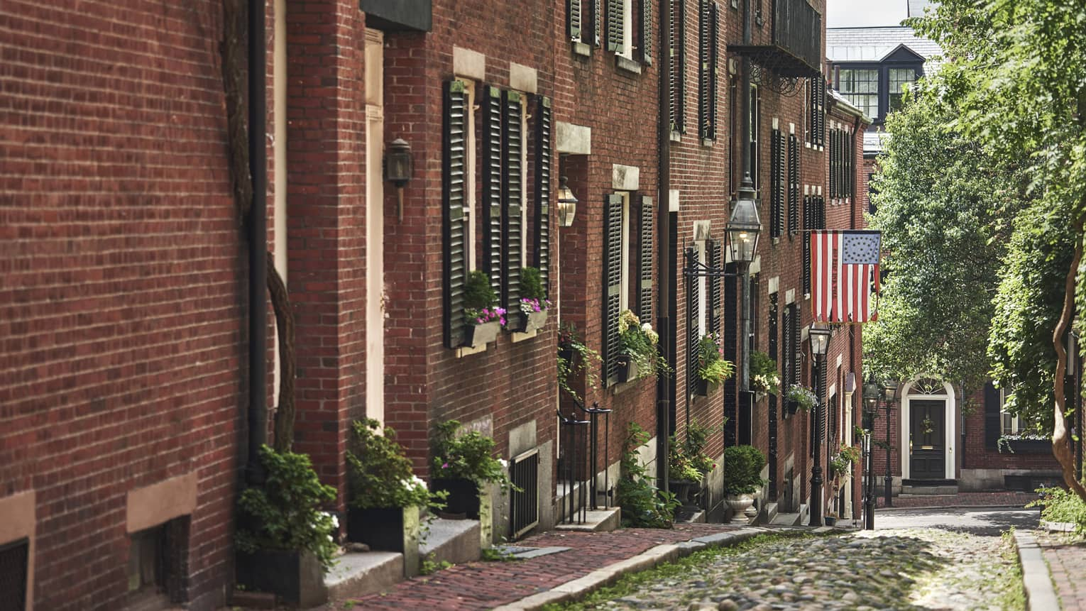 A cobblestone alley in Beacon Hill, lined with red brick residential buildings