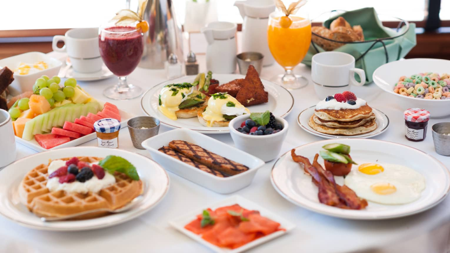 Brunch spread over white table, fresh waffles, bacon, eggs benedict, fruit platters