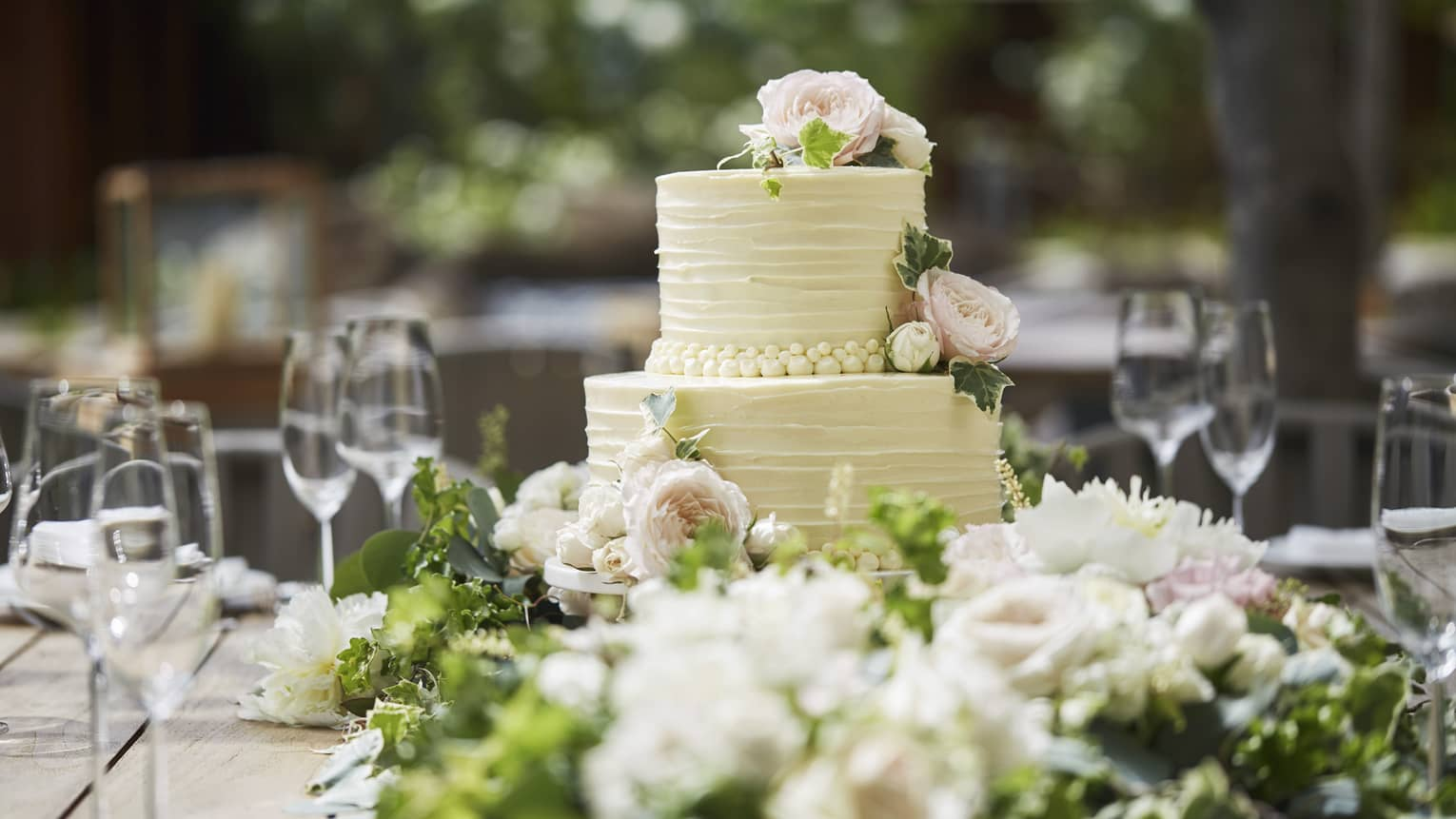 Two-tiered white wedding cake on banquet table with wine glasses, flowers