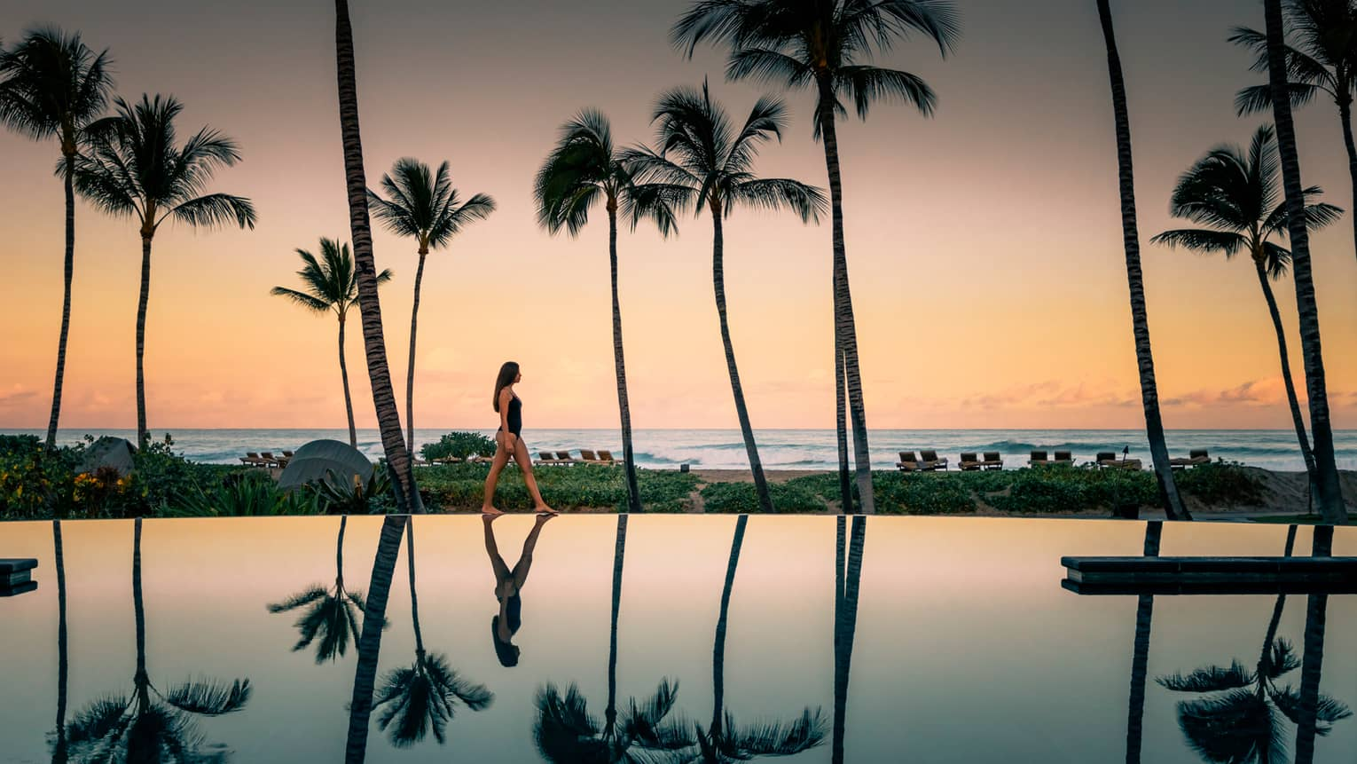 Woman in swimsuit walks by Palm Grove Pool at sunset, palm trees reflected on surface