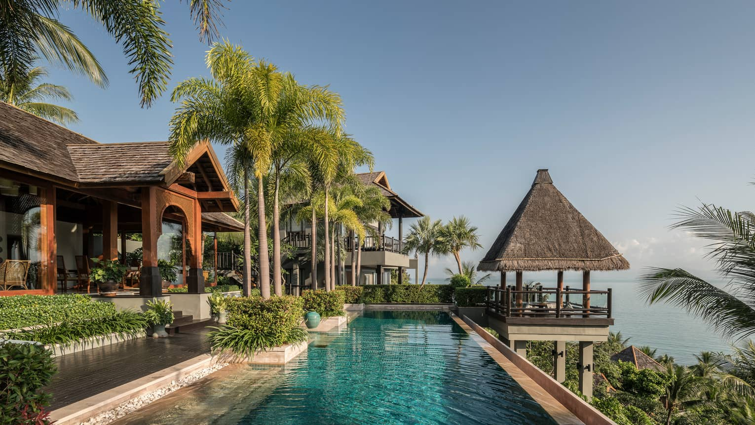Long outdoor swimming pool under tall palm trees, thatched roof gazebo