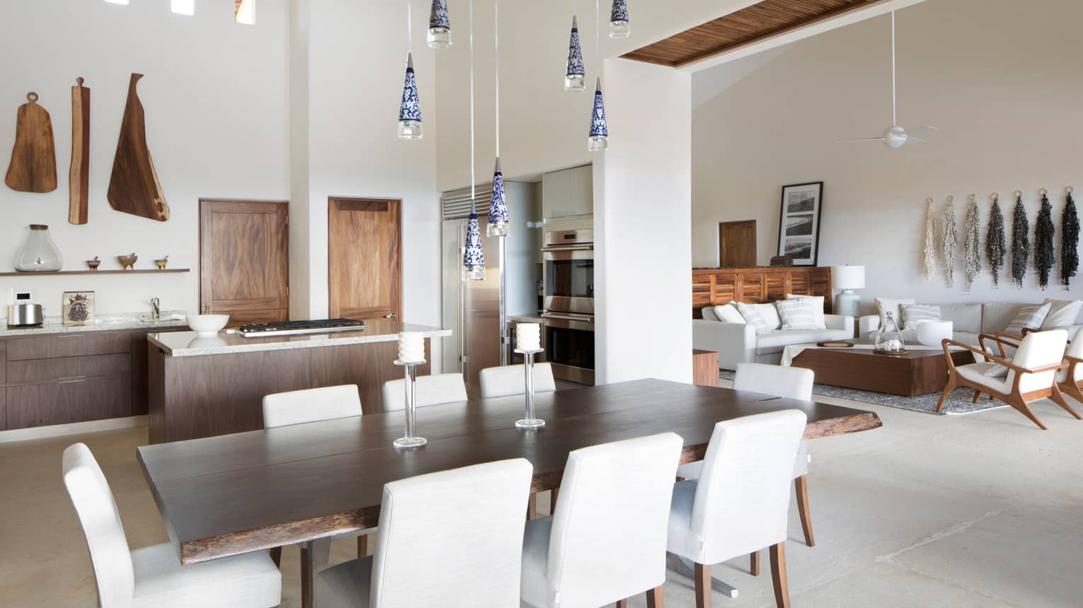 White dining chairs around long wood table under glass lights, modern kitchen