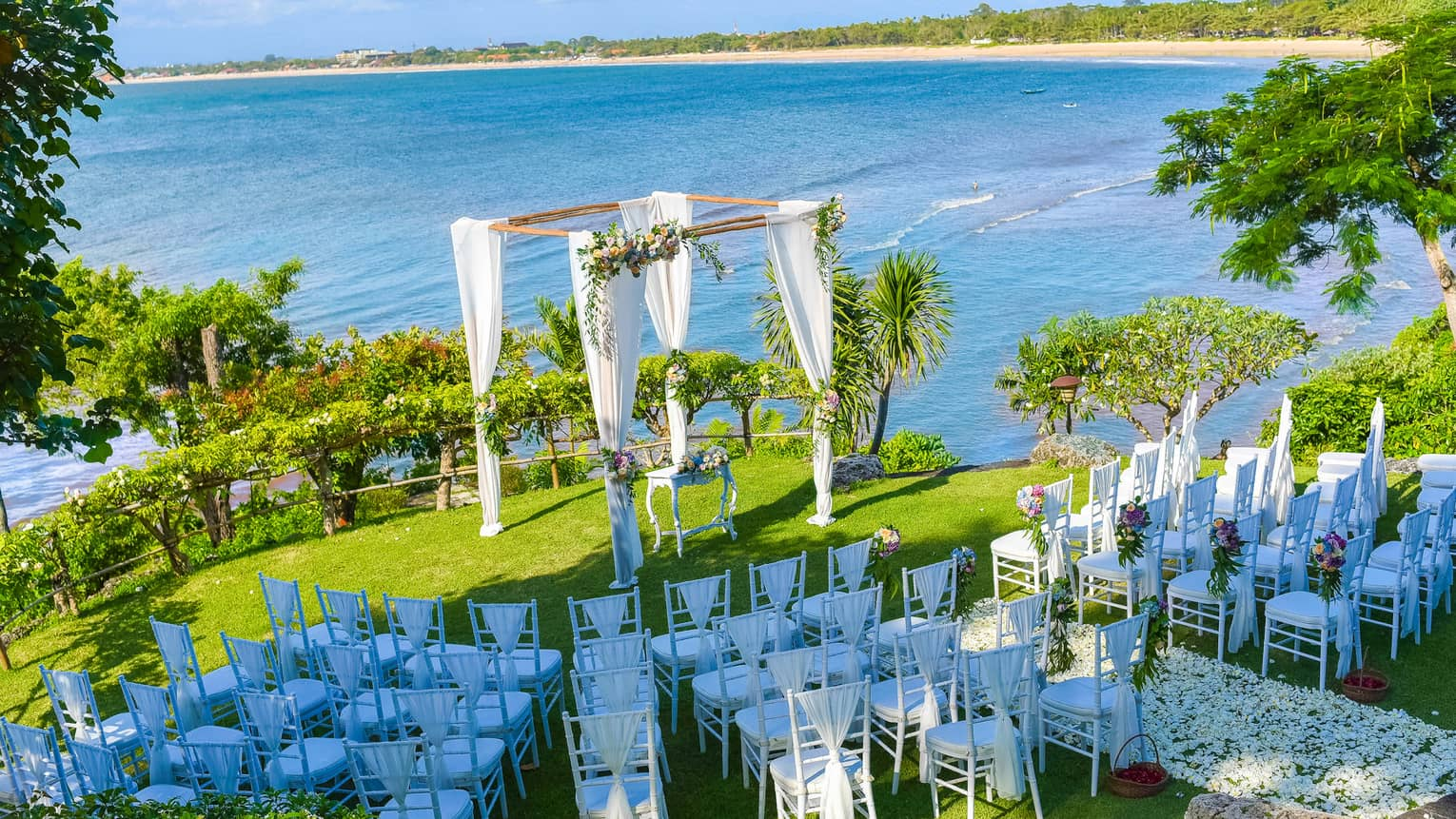Aerial view of rows of white chairs facing wedding altar on lawn by ocean