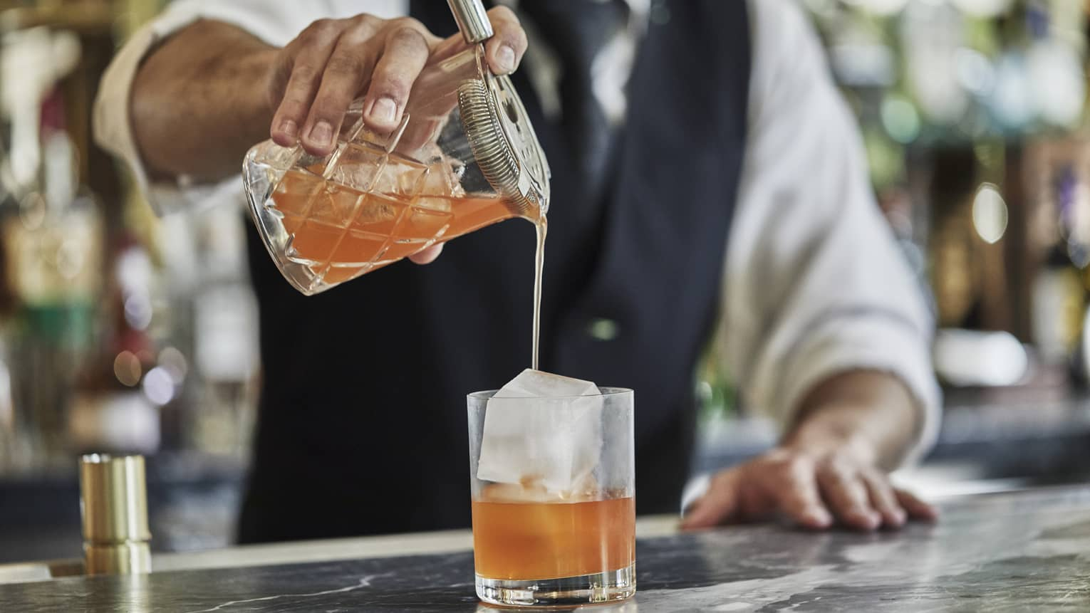 Close-up of bartender pouring orange cocktail from shaker into crystal glass with large ice cube