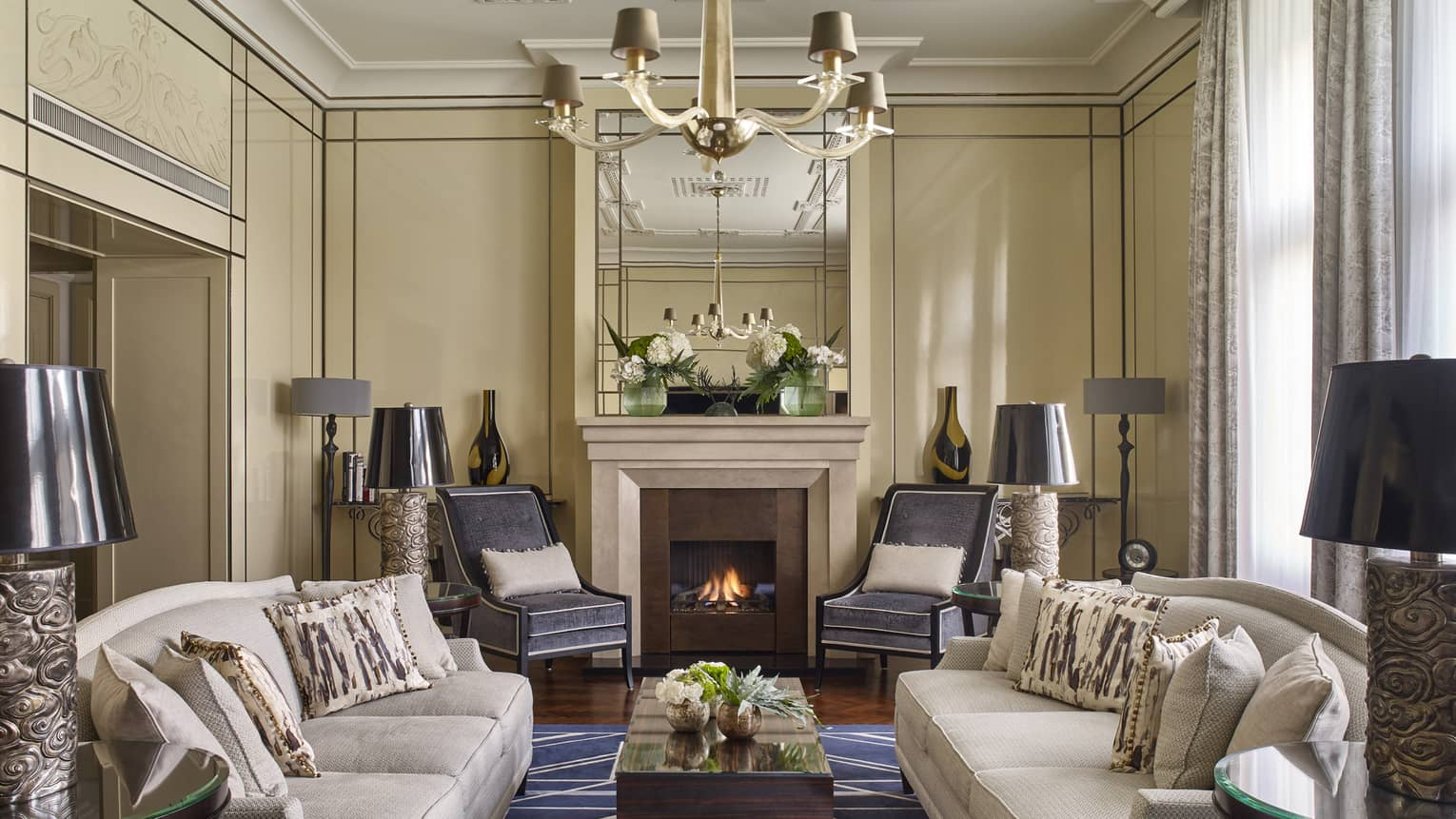 Grand sitting room in Royal Suite with fireplace, two couches, rug, lamps, drapes
