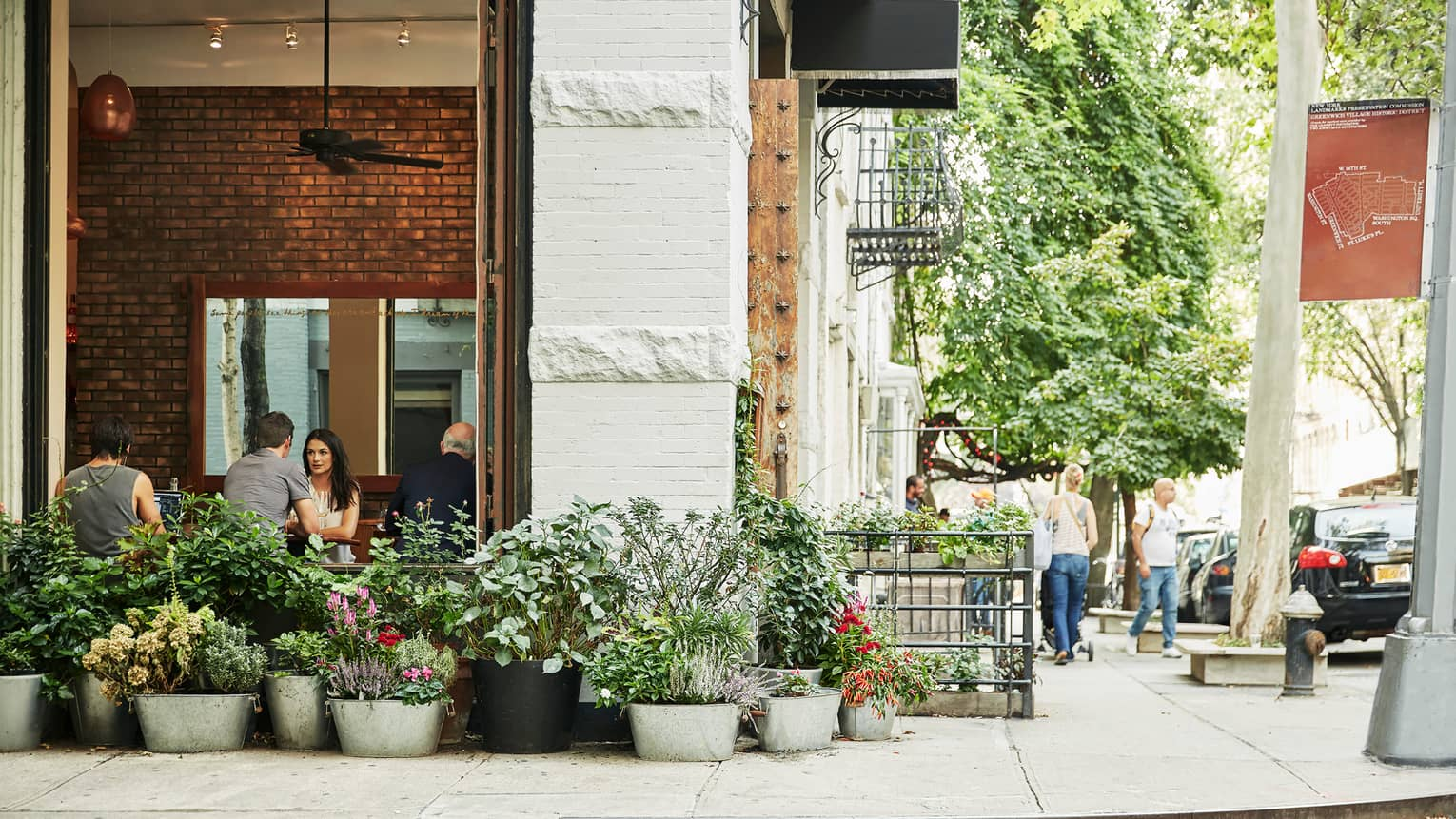 Exterior view of building on city corner, diners by open window with metal planters, flowers