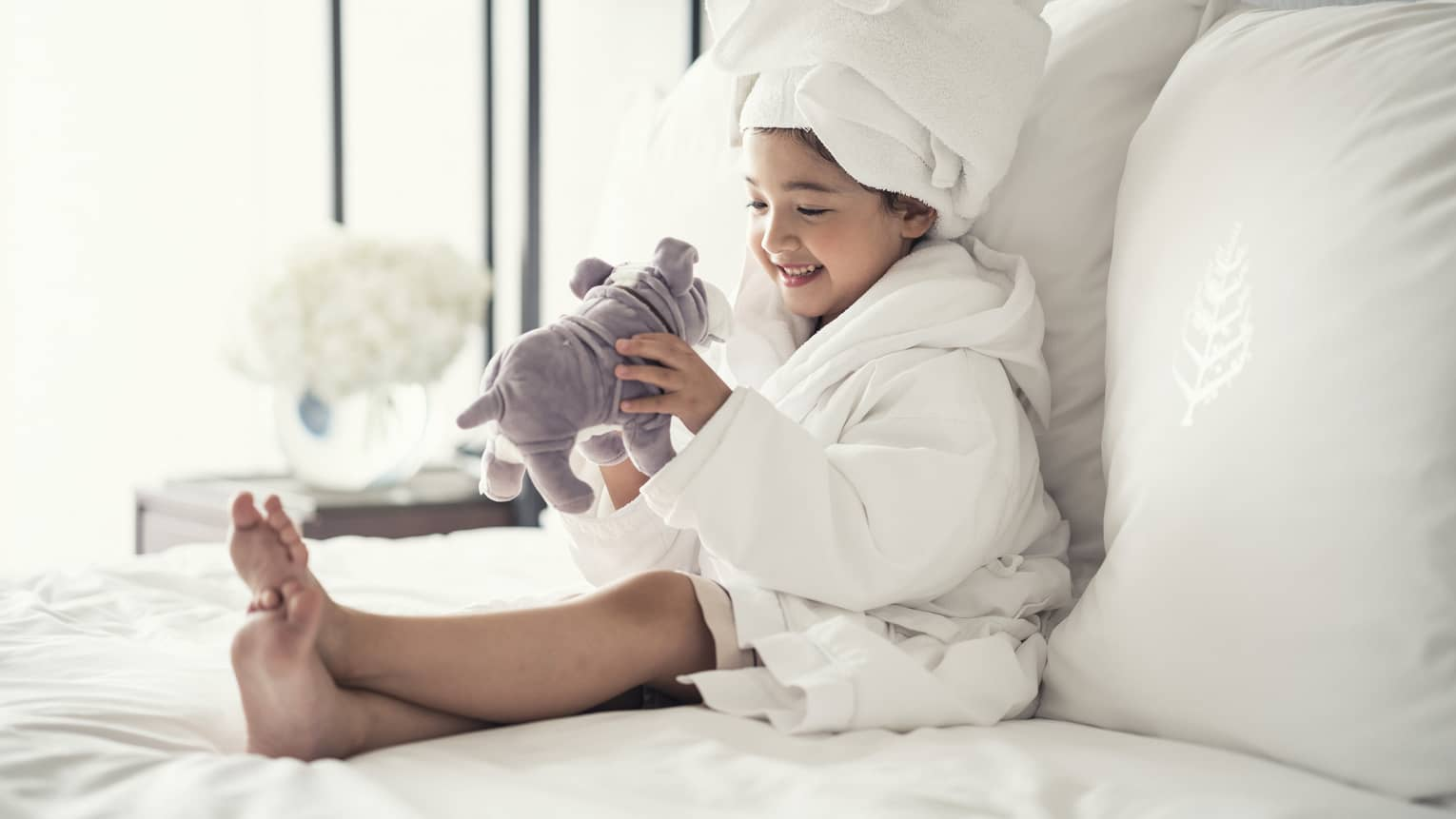 Young girl wearing white bathrobe, towel around head plays with stuffed dog on bed