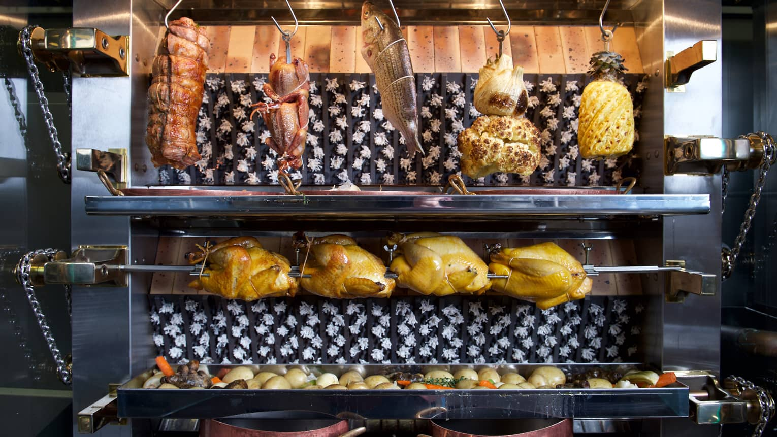 Whole chickens on rotisserie under whole fish, cauliflower hanging from hooks