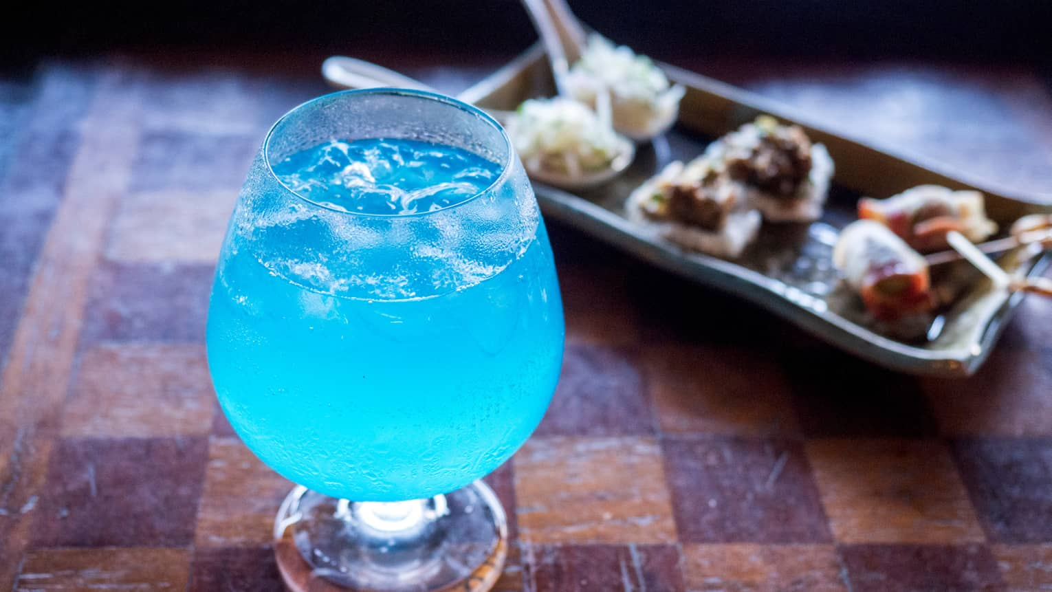 Bright blue cocktail in glass beside platter with small appetizers