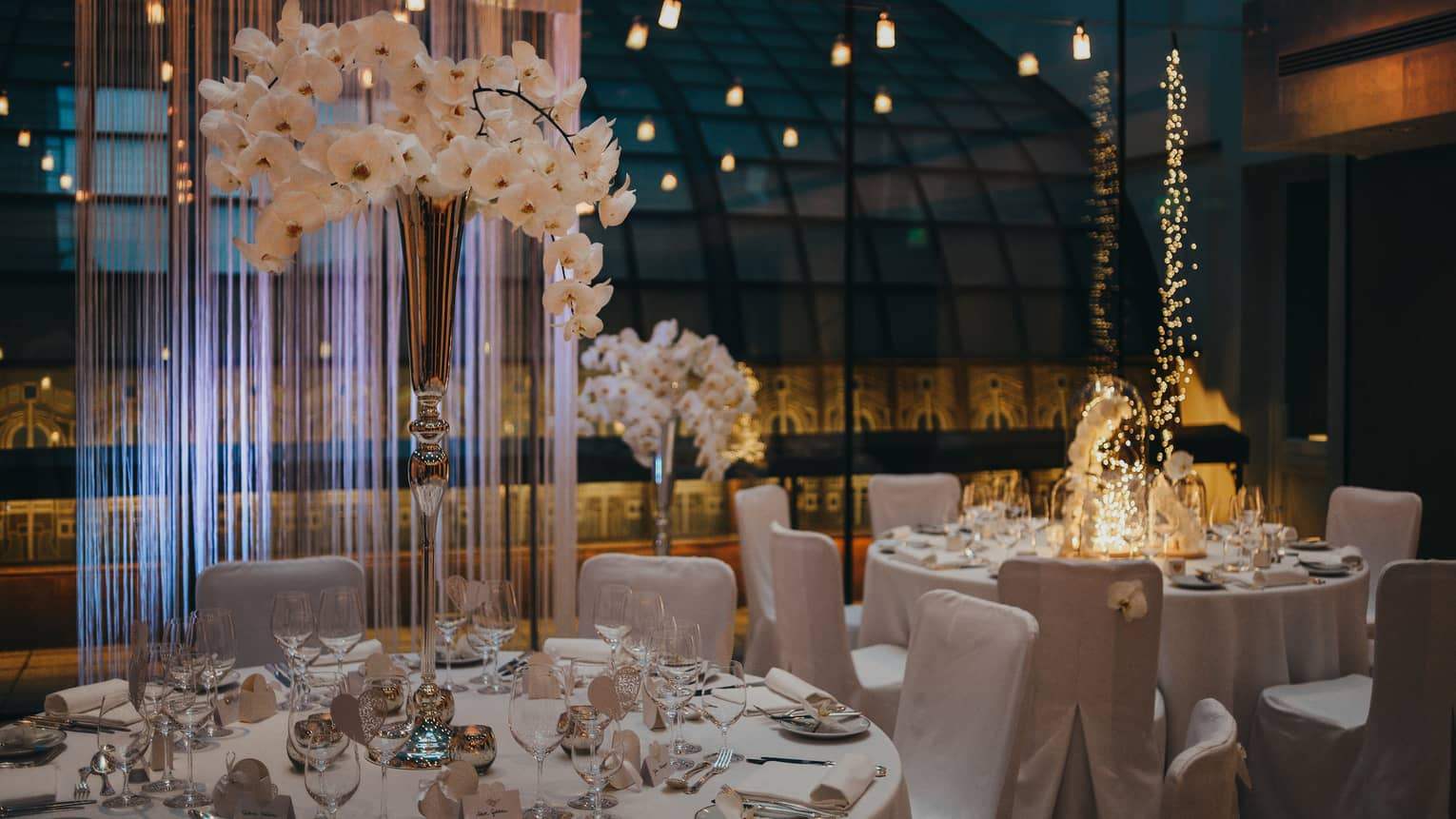 White dining tables and chairs with vase of orchids beside glass wall and reflecting lights