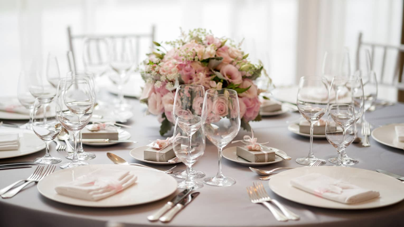 Wedding reception table setting with pink rose floral centrepiece
