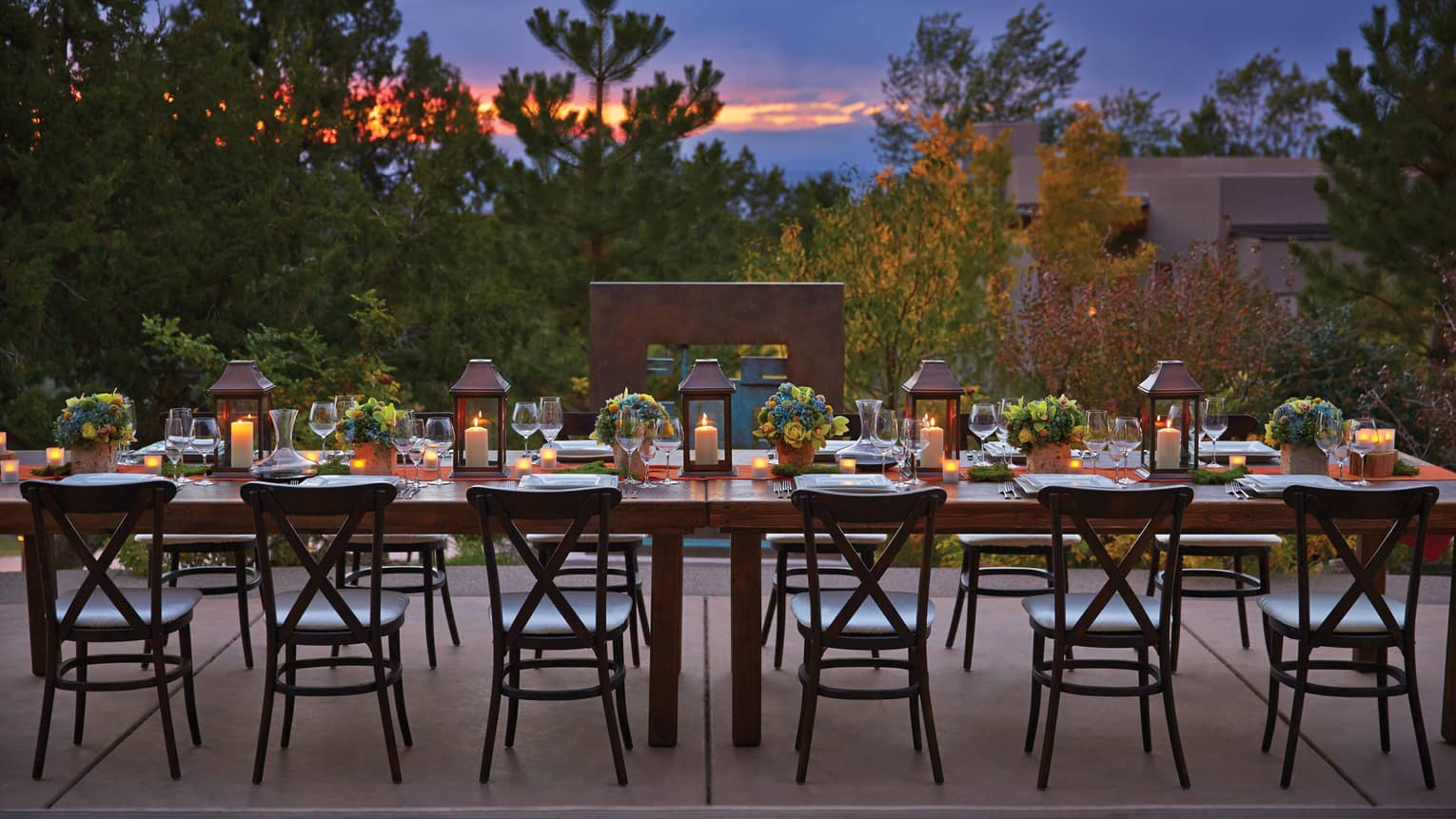 Long, candle-lit dining table on Terra patio at sunset