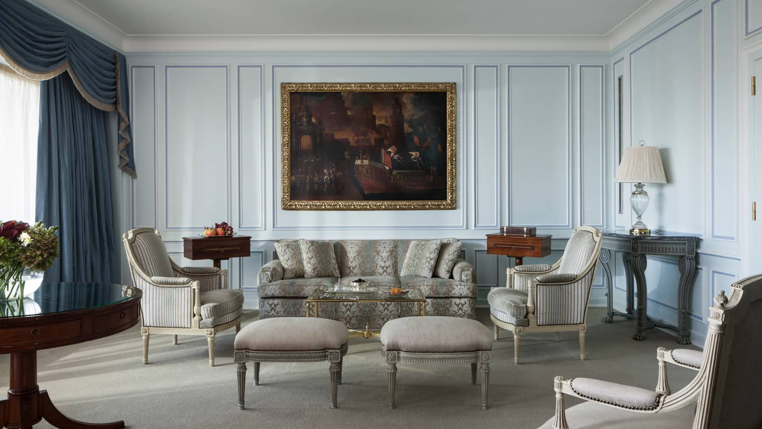 Sunny Grand One-Bedroom Suite with light grey-and-blue velvet sofa, chairs, large oil painting with gold frame